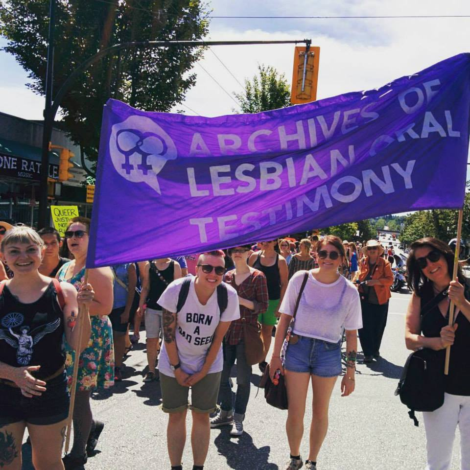 "[ALOT at a pride march, two people hold up a banner reading ""Archives of Lesbian Oral Testimony""]"