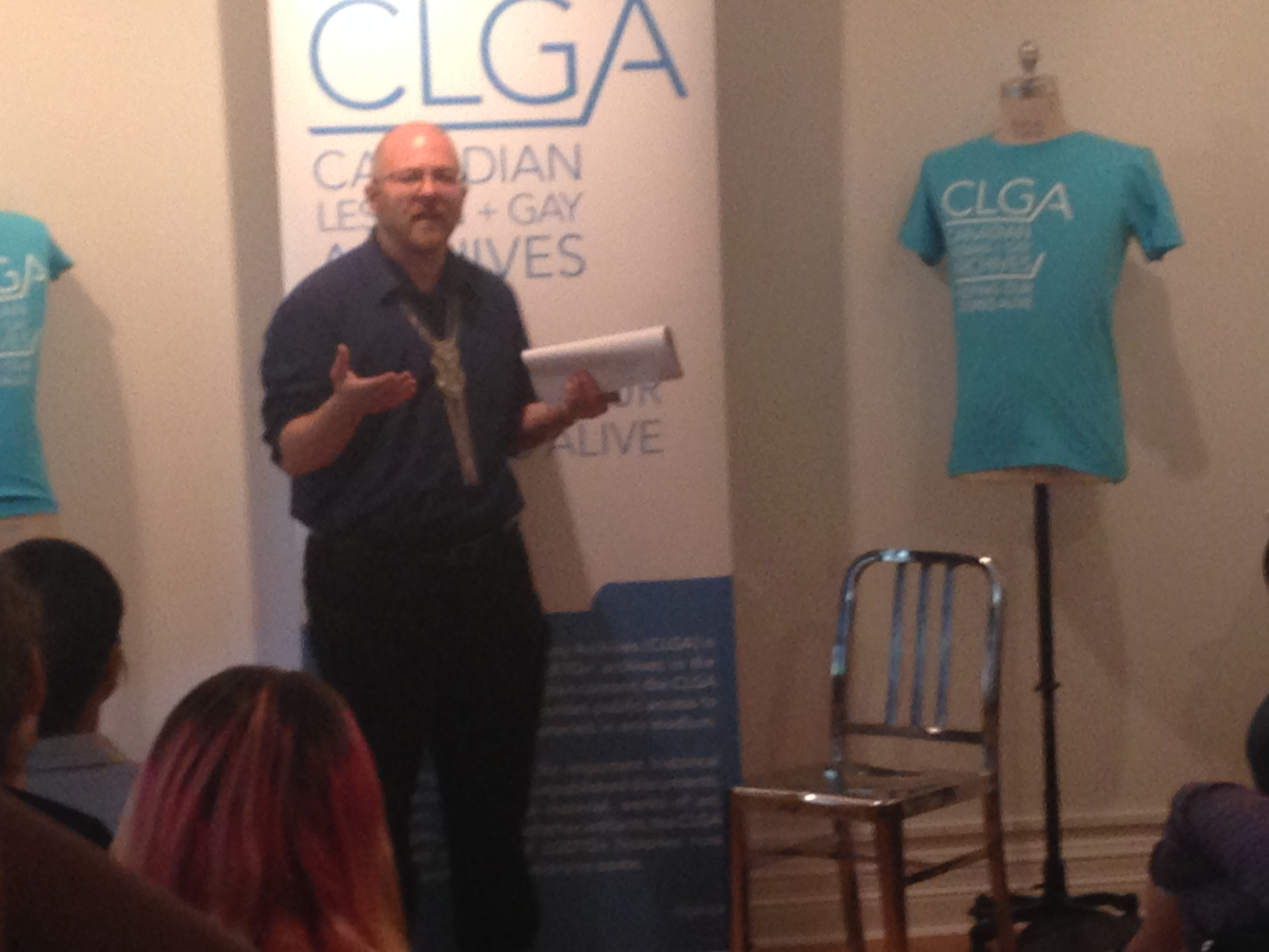 [Nick stands in front of a CLGA banner speaking to the crowd""