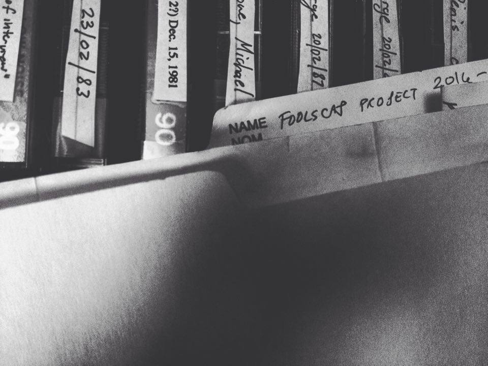 "[photo of a folder on top of multiple audio tapes, text on the folder reads ""foolscap project 2016-"""