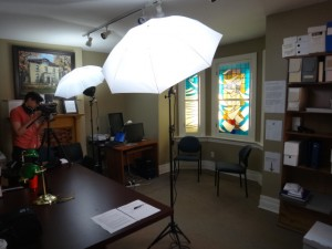 [photo of lighting equipment set up in the reading room with a person operating a camera in the background]