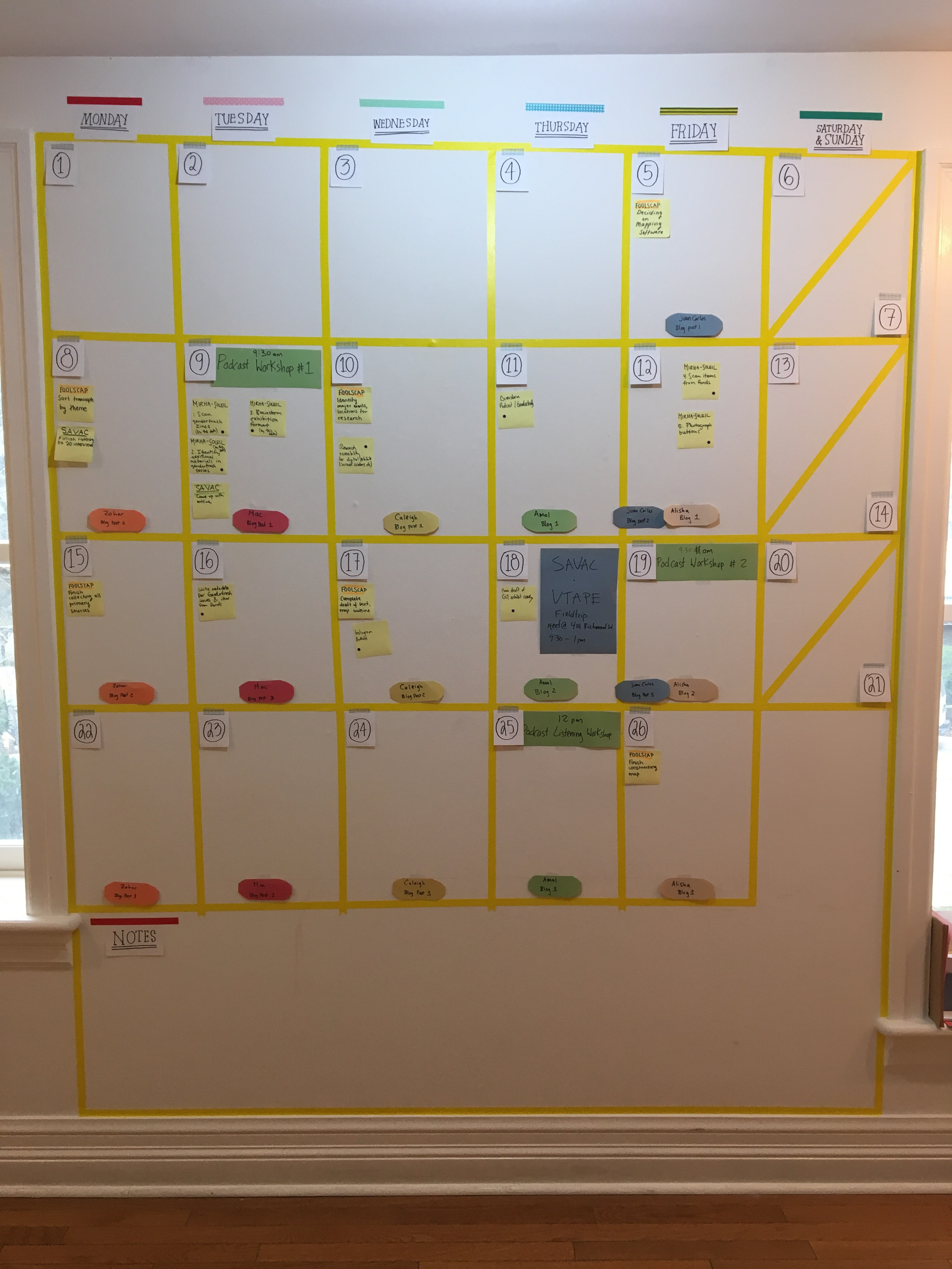 Photo of a large wall Calendar for Scholars in Residence Digital Collections Lab at Canadian Lesbian and Gay Archives. Made of yellow tape against a white wall and filled in using post-it notes and other stick-on papers.