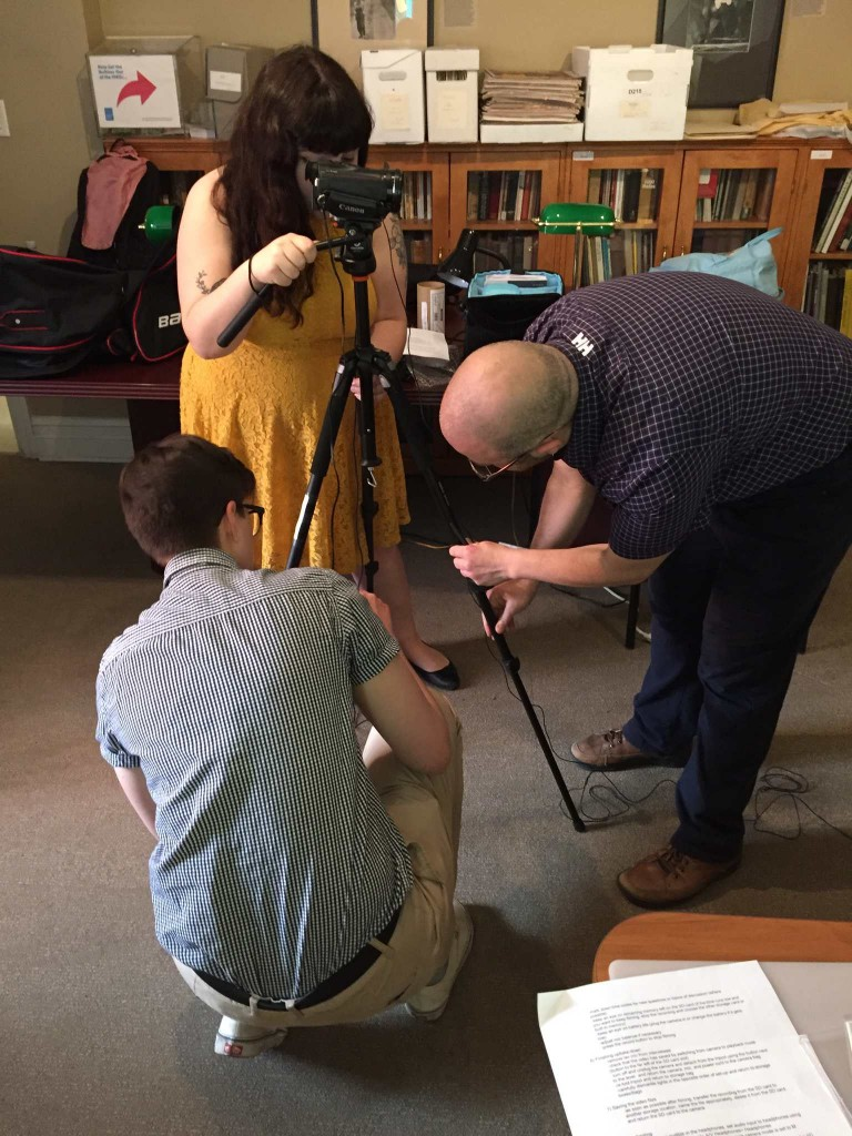 [One person looks into viewfinder of camera on tripod, two other people adjust the tripod]