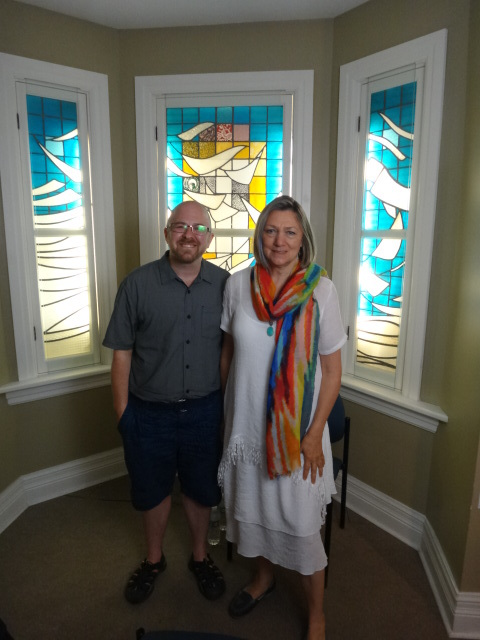 a man and a woman stand in front of a stained glass window