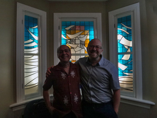 two men stand in front of a stained glass window